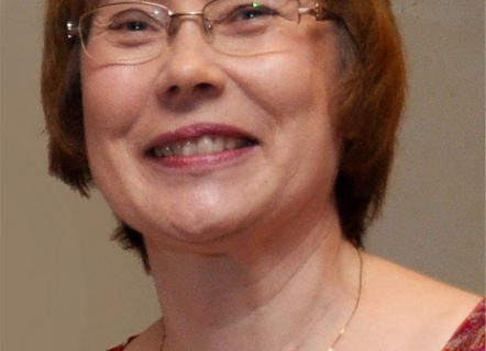 Portrait of a smiling woman with fair skin, short brown hair and glasses. She's wearing a red silk dress and a fine gold chain
