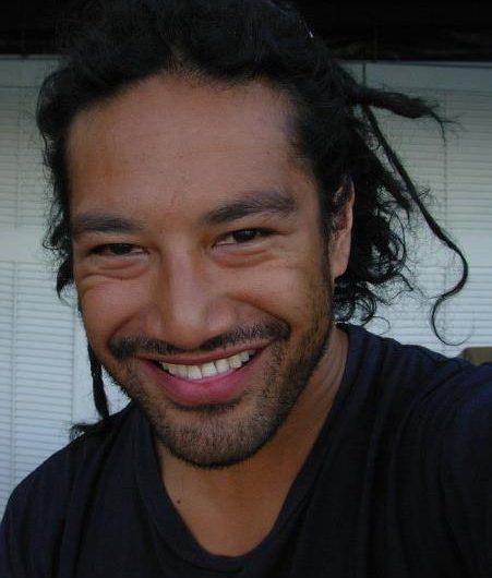 A close up photo of a man in a dark shirt with stubble and dreadlocks that are pulled back into a bun. He is smiling at the camera