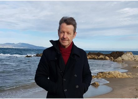 Man standing on a beach, smiling and looking at the camera, wearing a maroon sweater and dark jacket with collar turned up and hands in the jacket pockets, squinting against the wind and with hair blowing back. Small waves are washing across the sand just behind the man and a line of rocks forms a small cove. Further in the distance, on the left is a headland and on the right the sea and horizon can be seen just above the rocks. The sky is luminous and dashed with swirling silver grey clouds