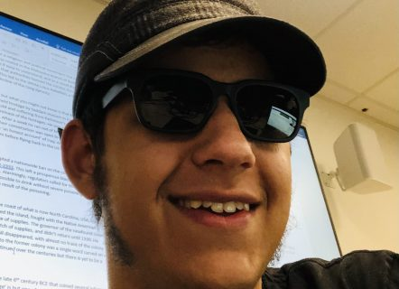 A young man wearing sunglasses and a cap is facing the camera at an angle, he is smiling in front of a projector screen. His sideburns are grown out and the top set of his teeth are showing