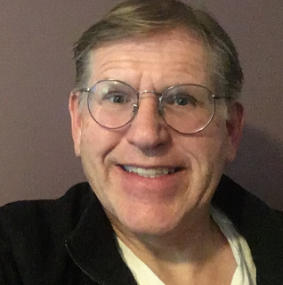 Self-portrait picture of a mature man. The picture is cut off at the chest and is taken before a grey background. He is wearing glasses. His hair is light blonde, slightly grey and is parted on the left side. The man is smiling with teeth. He is wearing glass, a black top with an open zip over a white t-shirt
