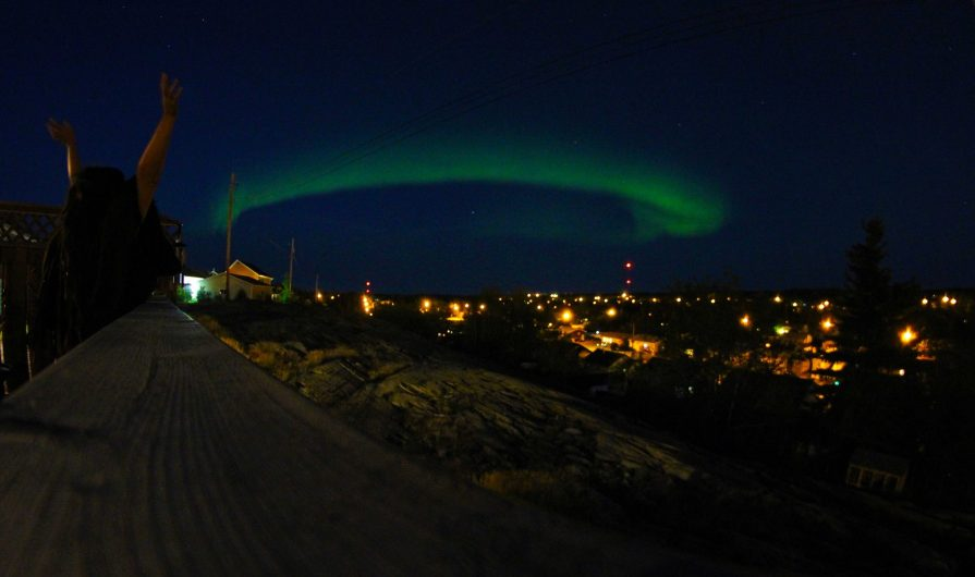 A person throwing their hands up in the air while out at night. Houses light up the darkness. There's a green aurora in the sky.