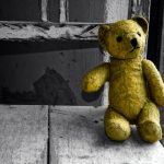 Old yellow teddy bear on an old flaking white wooden chair.