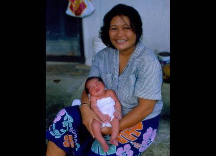 A Polynesian lady with a big smile, dressed in a bright sarong, holding a newborn baby.