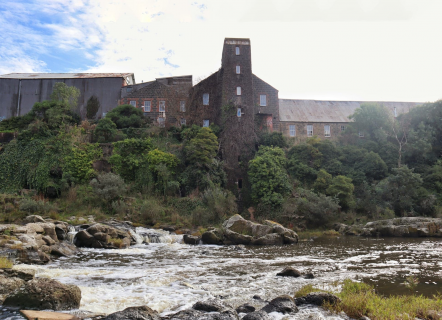 To the left is a large silver warehouse. Centre and right are large brick building covered in moss. There are a range of mostly dark green trees in front. At the very foreground is a river with large rocks.