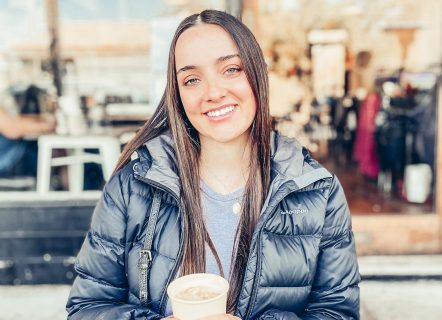 A young woman with long brown hair and wearing a black puffer jacket. She is seated at a table holding a takeaway cup of coffee and smiling at the camera