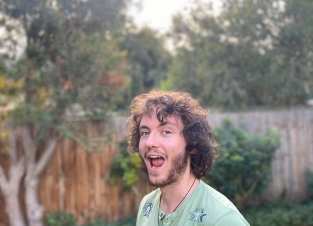 A youthful man with wild brown curls and a short scruffy beard. He is wearing a mint panthers t-shirt, smiling with his mouth wide open, and standing in an open backyard