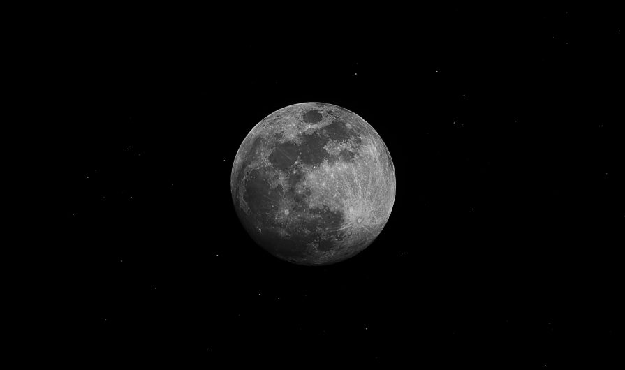 Black and white photograph of the moon in a black sky.