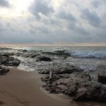 A beach with large rocks. The sand is wet and dark. There are small waves coming in and the sky is cloudy