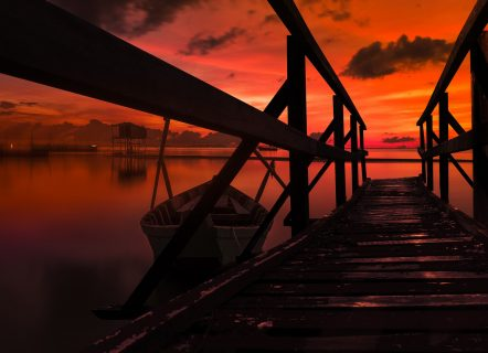 A wooden pier and small wooden boat looking over the ocean. The sunset is red and colouring everything in warm red colours.