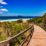 Brown wooden walkway with wooden rails leads down to a beach. The water is visible and calm. On the sides of the walkway are wild flora. The sky is clear with few clouds.