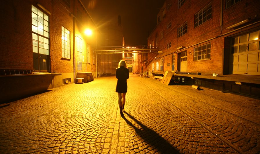 Woman in dark dress and medium light hair walking down street at night, facing away from camera. The street is lined with brick buildings and a bright yellow streetlight lights the woman and cobblestone path