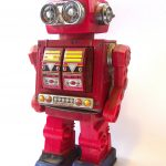 Red children's toy robot. Has silver eyes, a panel on the torso and blue feet.